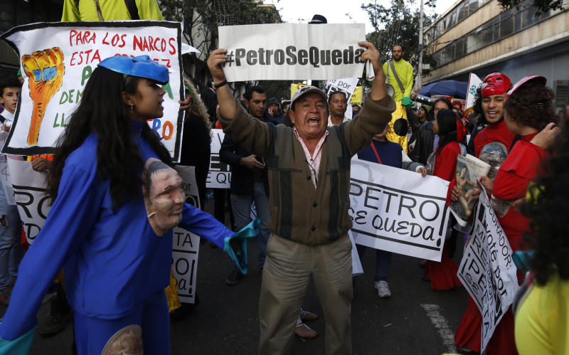 """A supporters of Bogota's Mayor Gustavo Petro holds a sign that reads in Spanish: """"Petro Stays,"""" during a rally of thousands of people against Colombia's inspector-general Alejandro Ordonez in Bogota, Colombia, Friday, Dec. 13, 2013. Ordonez ordered Petro removed from office over alleged mismanagement of the garbage-collection system. (AP Photo/Fernando Vergara)"""