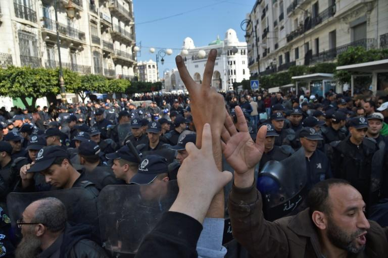 Algerian security forces encircle an anti-government demonstration in Algiers on February 18