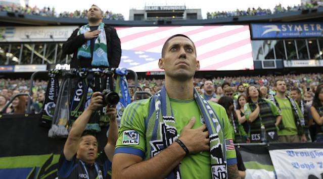 Clint Dempsey, captain of the U.S. National Soccer Team, stands for the singing of the national anthem after he was introduced as the newest member of the Seattle Sounders FC MLS soccer team, Saturday, Aug. 3, 2013, prior to a match between the Sounders and FC Dallas in Seattle. Dempsey previously played for Tottenham Hotspur in the English Premier League. (AP Photo/Ted S. Warren)