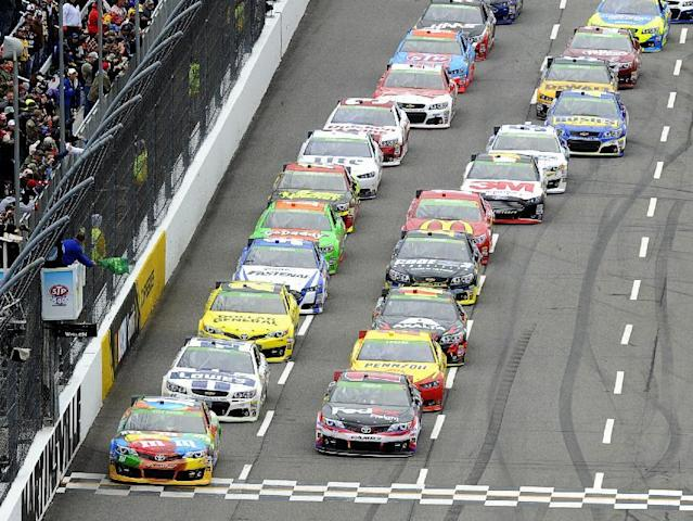 Driver Kyle Busch (18) leads the field to the green flag for the start of a NASCAR Sprint Cup Series auto race at Martinsville Speedway, Sunday, March 30, 2014, in Martinsville, Va. (AP Photo/Mike McCarn)
