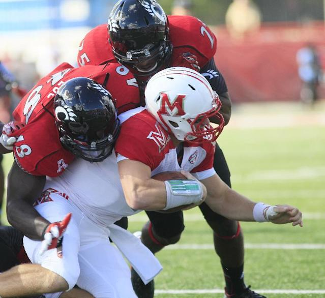 Miami (Ohio) quarterback Austin Boucher (16) is tackled by Cincinnati's Jeff Luc, left, and Arryn Chenault during the first half of an NCAA college football game, Saturday, Sept. 21, 2013, in Oxford, Ohio. (AP Photo/Tony Tribble)