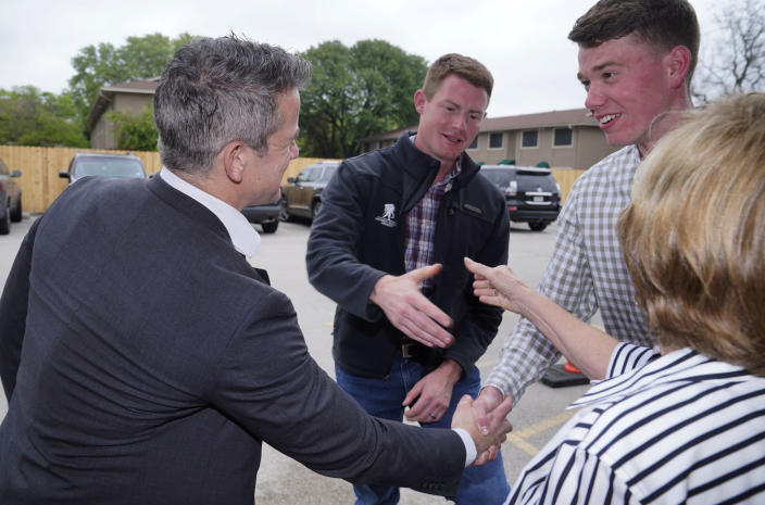 Rep. Adam Kinzinger, R-Ill., left, shakes hands with Grant Goodyear, right, as Texas congressional candidate Michael Wood, center, shakes hands with Linda Thomas Tuesday, April 27, 2021, in Arlington, Texas. Wood is considered the anti-Trump Republican Texas congressional candidate that Kinzinger has endorsed in the May 1st special election for the 6th Congressional District. (AP Photo/LM Otero)