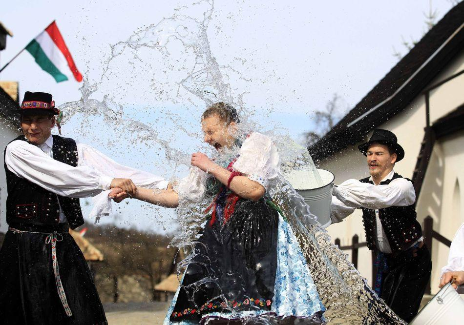 "Men throw water onto a woman as part of traditional Easter celebrations, during a media presentation in Holloko, 100 km (62 miles) east of Budapest, March 28, 2012. Locals from the World Heritage village of Holloko, celebrate Easter with the tradition ""watering of the girls"", a Hungarian tribal fertility ritual rooted in the area's pre-Christian past."