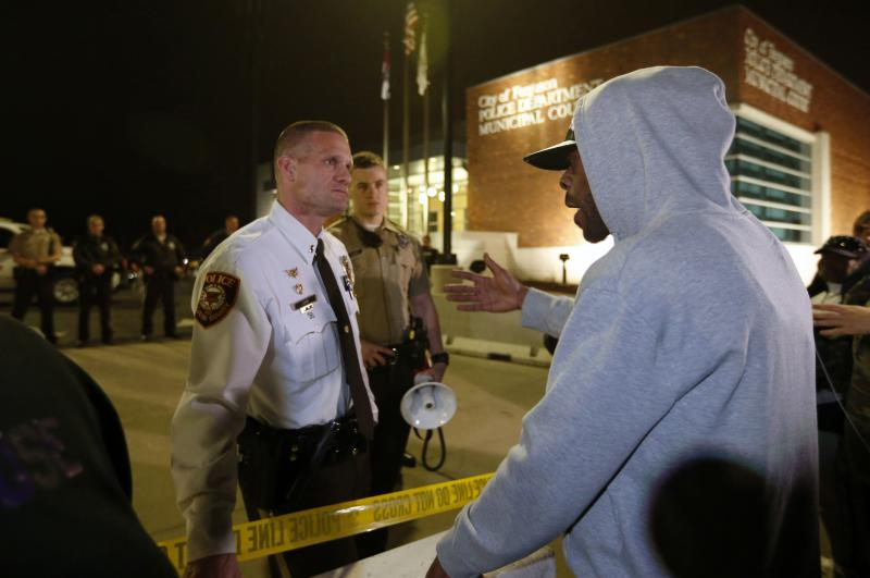 A protester talks with a police officer in front of the Ferguson Police Department
