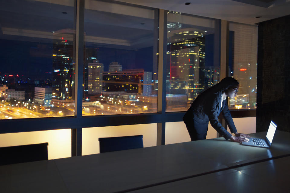 Work colleague views computer in conference room at night