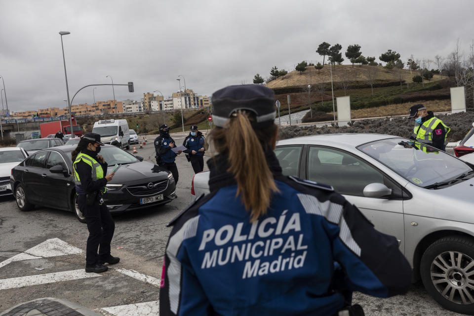 A police officer checks a driver's documents at a checkpoint on the outskirts of Madrid, Spain, Monday, Jan. 25, 2021. With several regions reporting Friday new daily records of infections, some regional governments are toughening their response. The central Madrid region, home to 6.6 million, brought its curfew from midnight to 10 p.m. starting on Monday, and ordered shop, bar and restaurant closures at 9 p.m. the latest. (AP Photo/Bernat Armangue)