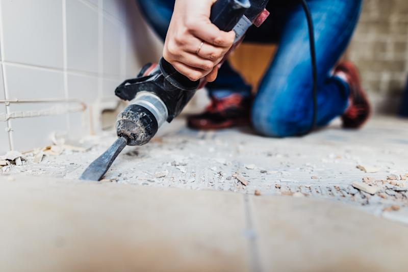 Woman removing old tiles, renovating the bathroom.