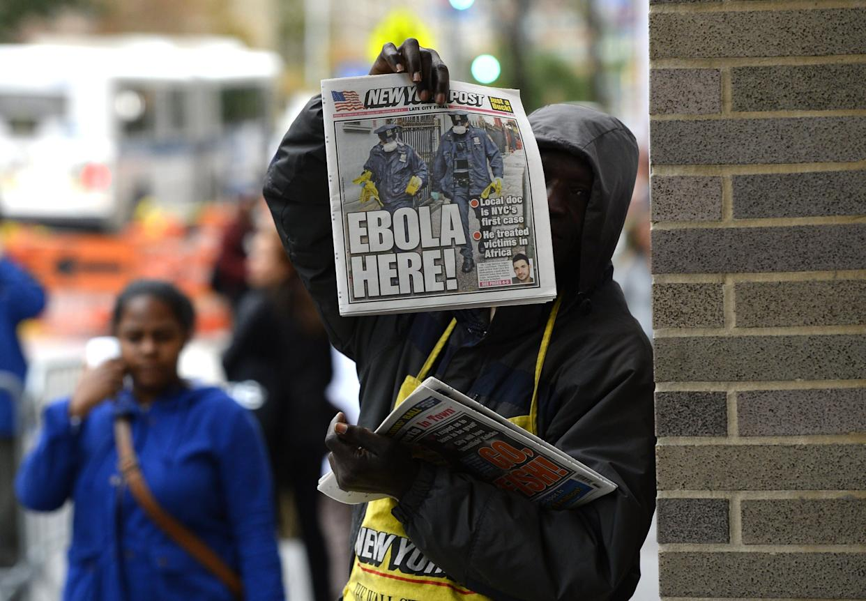 A newspaper vendor holds up a copy of the NY Post in front of the entrance to Bellevue Hospital October 24, 2014 in New York, the morning after it was confirmed that Craig Spencer, a member of Doctors Without Borders, who recently returned to New York from Guinea tested positive for Ebola.