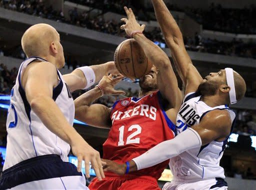 Philadelphia 76ers forward Evan Turner (12) is pressured by Dallas Mavericks center Chris Kaman (35) and guard Vince Carter (25) under the basket while trying to grab a rebound during the first half of an NBA basketball game, Tuesday, Dec. 18, 2012, in Dallas. (AP Photo/John F. Rhodes)
