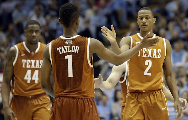 Texas' Isaiah Taylor (1) and Demarcus Holland (2) react following a play against North Carolina during the second half of an NCAA college basketball game in Chapel Hill, N.C., Wednesday, Dec. 18, 2013. At left is Texas' Prince Ibeh (44). Texas won 86-83. (AP Photo/Gerry Broome)