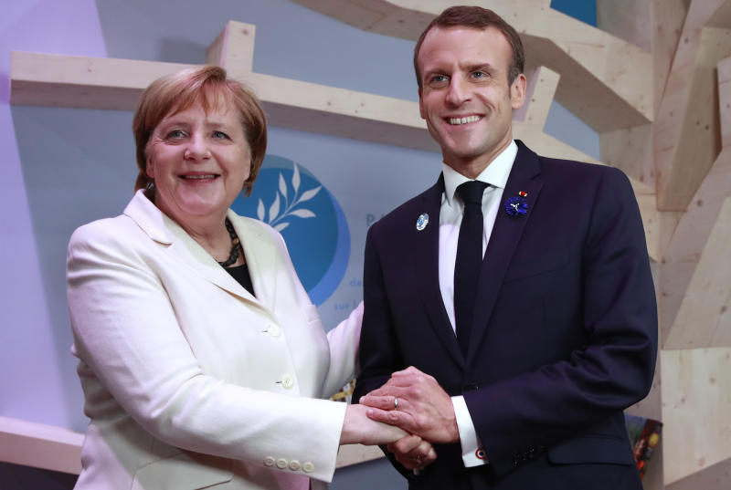 German Chancellor Angela Merkel and French President Emmanuel Macron hold hands after leaving books at the peace library of the Paris Peace Forum as part of the commemoration ceremony for Armistice Day, in Paris, Sunday, Nov. 11, 2018. International leaders attended a ceremony in Paris on Sunday at mark the 100th anniversary of the end of World War I. (Gonzalo Fuentes, Pool via AP)
