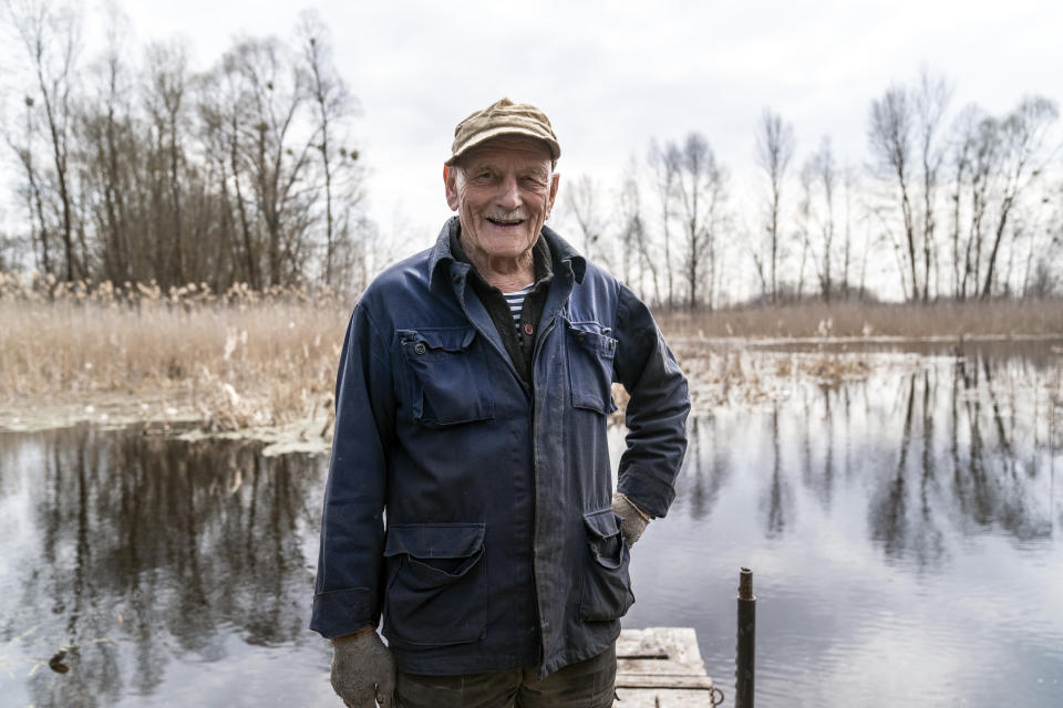"Yevgeny Markevich, a 85-year-old former teacher, smiles smiles during his interview with the Associated Press at the Chernobyl exclusion zone, Ukraine, Wednesday, April 14, 2021. Markevich said ""It's a great happiness to live at home, but it's sad that it's not as it used to be."" Today, he grows potatoes and cucumbers on his garden plot, which he takes for tests ""in order to partially protect myself."" The vast and empty Chernobyl Exclusion Zone around the site of the world's worst nuclear accident is a baleful monument to human mistakes. Yet 35 years after a power plant reactor exploded, Ukrainians also look to it for inspiration, solace and income. (AP Photo/Evgeniy Maloletka)"