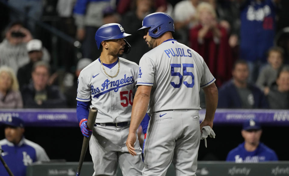 Los Angeles Dodgers' Mookie Betts, left, congratulates pinch-hitter Albert Pujols as he returns to the dugout after hitting an RBI-single off Colorado Rockies relief pitcher Jhoulys Chacin in the 10th inning of a baseball game Tuesday, Sept. 21, 2021, in Denver. The Dodgers won 5-4. (AP Photo/David Zalubowski)