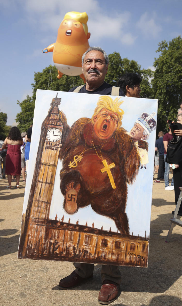 """<p>Political artist Kaya Mar holds a painting depicting Donald Trump, during protests in London, July 13, 2018. Trump's pomp-filled welcome to Britain was overshadowed Friday by an explosive interview in which he blasted Prime Minister Theresa May, blamed London's mayor for terror attacks against the city and argued that Europe was """"losing its culture"""" because of immigration. (Photo: Yui Mok/AP) </p>"""