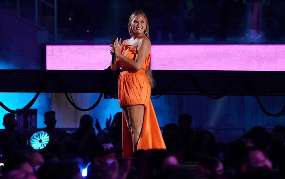 """Chrissy Teigen had a prepared speech, but she made a bigger impression on the SoFi Stadium audience with her amusing response after a verbal glitch during the """"Vax Live"""" concert on May 2, 2021."""