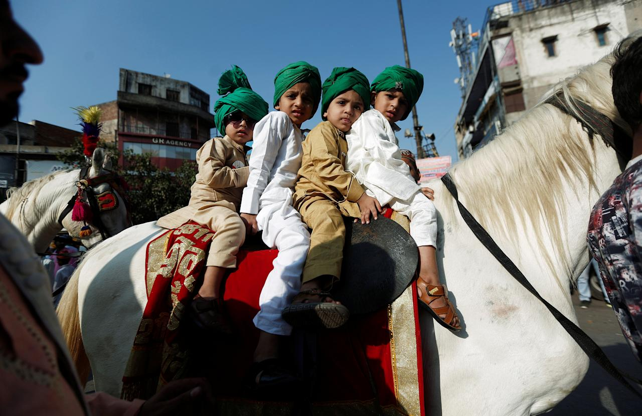 Muslim boys sit on a horse during a religious procession to mark Eid-e-Milad-ul-Nabi, or birthday celebrations of Prophet Mohammad, in the old quarters of Delhi, India, November 21, 2018. REUTERS/Adnan Abidi