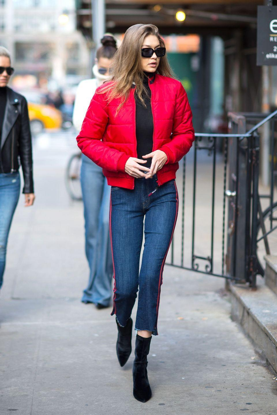 <p>In a red Tommy Hilfiger bomber, black sweater, red striped cropped flare Mother Denim, velvet booties and rectangular sunglasses while out in NYC. </p>