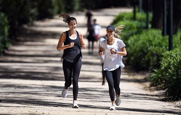 People enjoy the spring weather while jogging on a running track around Melbourne's Royal Botanic Gardens.