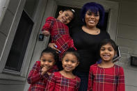 Dinora Torres, a MassBay Community College student, poses with her four daughters on the front porch of their home, Thursday, Jan. 14, 2021, in Milford, Mass. From front left are daughters Davina, Alana and Hope, with Faith in Dinora's arms. At the college, applications for meal assistance scholarships have increased 80% since last year. Among the recipients is Torres, who said the program helped keep her enrolled. (AP Photo/Charles Krupa)
