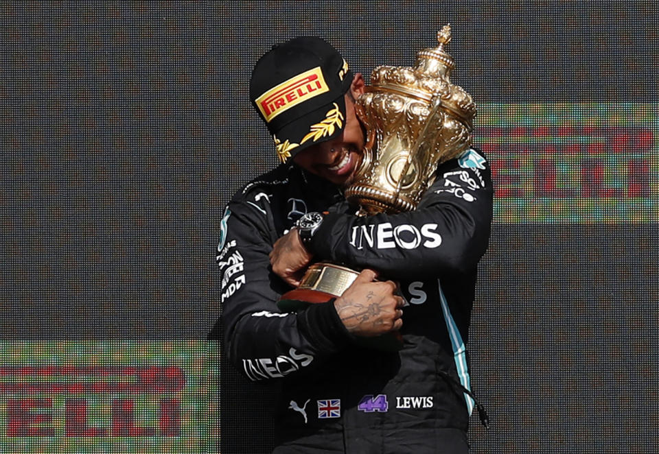 Mercedes' driver Lewis Hamilton (pictured) holds the trophy on the podium after the Formula One British Grand Prix motor race at Silverstone motor racing circuit in Silverstone, central England on July 18, 2021.