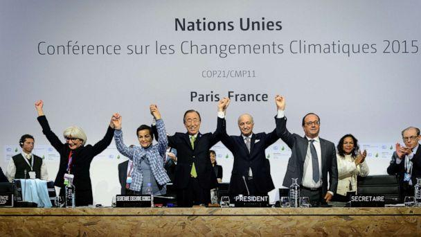 PHOTO: Executive Secretary of the United Nations Framework Convention on Climate Change (UNFCCC) raise hands together after adoption of a historic global warming pact at the COP21 Climate Conference in Le Bourget, north of Paris, Dec. 12, 2015. (COP21/Anadolu Agency/Getty Images)