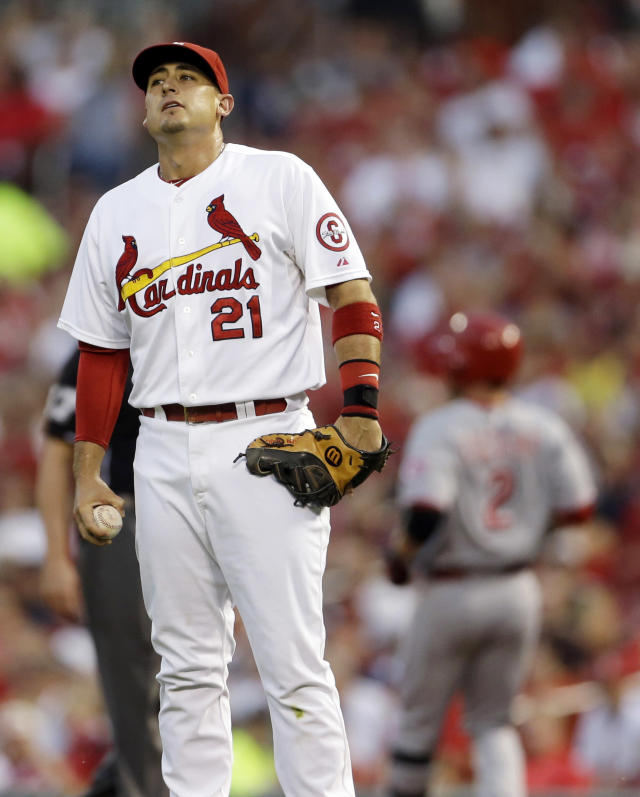 St. Louis Cardinals first baseman Allen Craig, left, pauses after Cincinnati Reds' Zack Cozart, right, reached first base with a single during the first inning of a baseball game Wednesday, Aug. 28, 2013, in St. Louis. (AP Photo/Jeff Roberson)