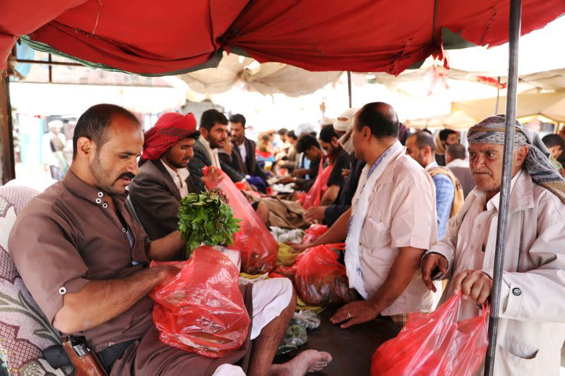 Vendor holds qat, a mild stimulant, at a qat market amid concerns of the spread of the coronavirus disease (COVID-19) in Sanaa