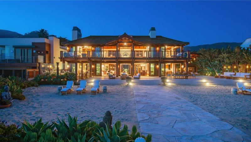 Spanning over an acre, the waterfront estate includes two homes and a saltwater pool that descends to 117 feet of beach.