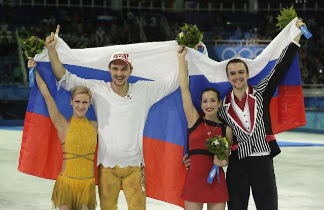 Tatiana Volosozhar and Maxim Trankov of Russia, left, and Ksenia Stolbova and Fedor Klimov of Russia celebrate after they placed first and second following the flower ceremony for the pairs free skate figure skating competition at the Iceberg Skating Palace during the 2014 Winter Olympics, Wednesday, Feb. 12, 2014, in Sochi, Russia. (AP Photo/Darron Cummings)