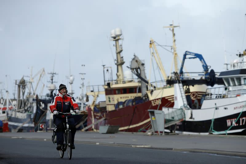 FILE PHOTO: A man rides his bicycle past a row of docked fishing ships in the village of Thyboron in Jutland, Denmark