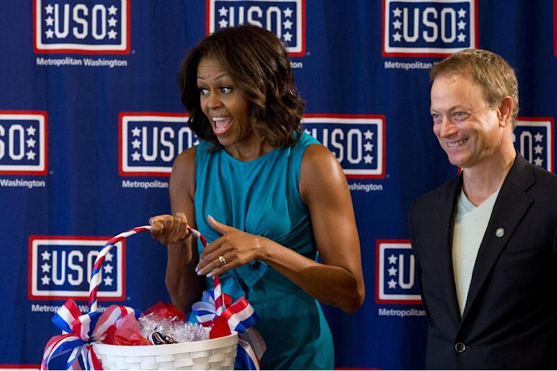 First lady Michelle Obama, accompanied by actor Gary Sinise, arrives for a visit to the USO Warrior and Family Center, holding a basket of dog-shaped cookies, Wednesday, Sept. 11, 2013, at Fort Belvoir, Va., during a service project to commemorate the Sept. 11th National Day of Service and Remembrance at Food and Friends. (AP Photo/Jacquelyn Martin)