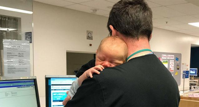 Dr. Muir Wallace of Waikato Hospital was pictured cuddling a baby while running the emergency department. (Photo: Facebook/ Waikato Hospital)