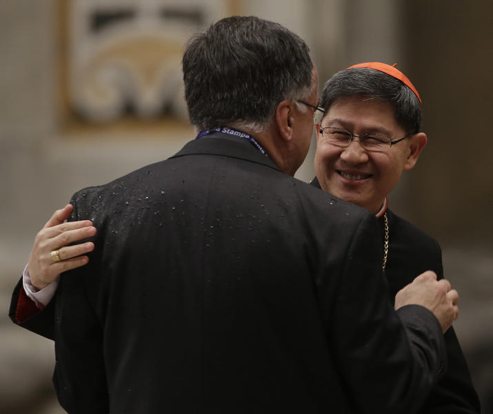 Cardinal Luis Antonio Tagle, right, is greeted by Father Thomas Rosica prior to the start of a vespers celebration in St. Peter's Basilica at the Vatican, Wednesday, March 6, 2013. (AP Photo/Gregorio Borgia)