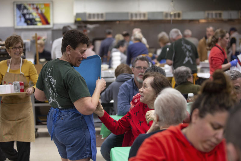 In this Feb. 28, 2020 photo, Ann Painter, center, is greeted by a diner as she serves meals during the a fish fry at Holy Angels parish in Pittsburgh, Pa. On March 12, Pittsburgh Bishop David Zubik suggested that people enjoy the fish fries with a take-out order rather than dining in due to virus concerns. (AP Photo/Rebecca Droke)