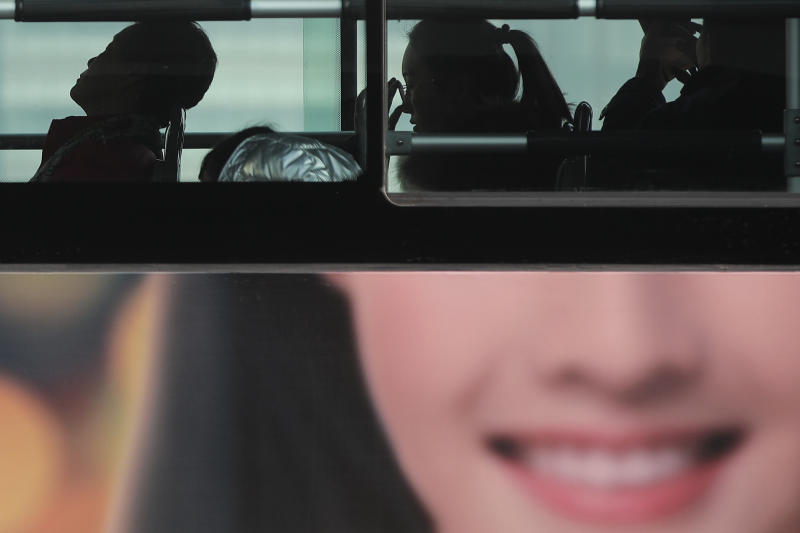 In this Jan. 12, 2019, photo, commuters ride on a bus with a smiling face advertisement at the Central Business District in Beijing. China's slowing economy is squeezing the urban workers and entrepreneurs the ruling Communist Party is counting on to help transform this country from a low-wage factory floor into a prosperous consumer market. (AP Photo/Andy Wong)