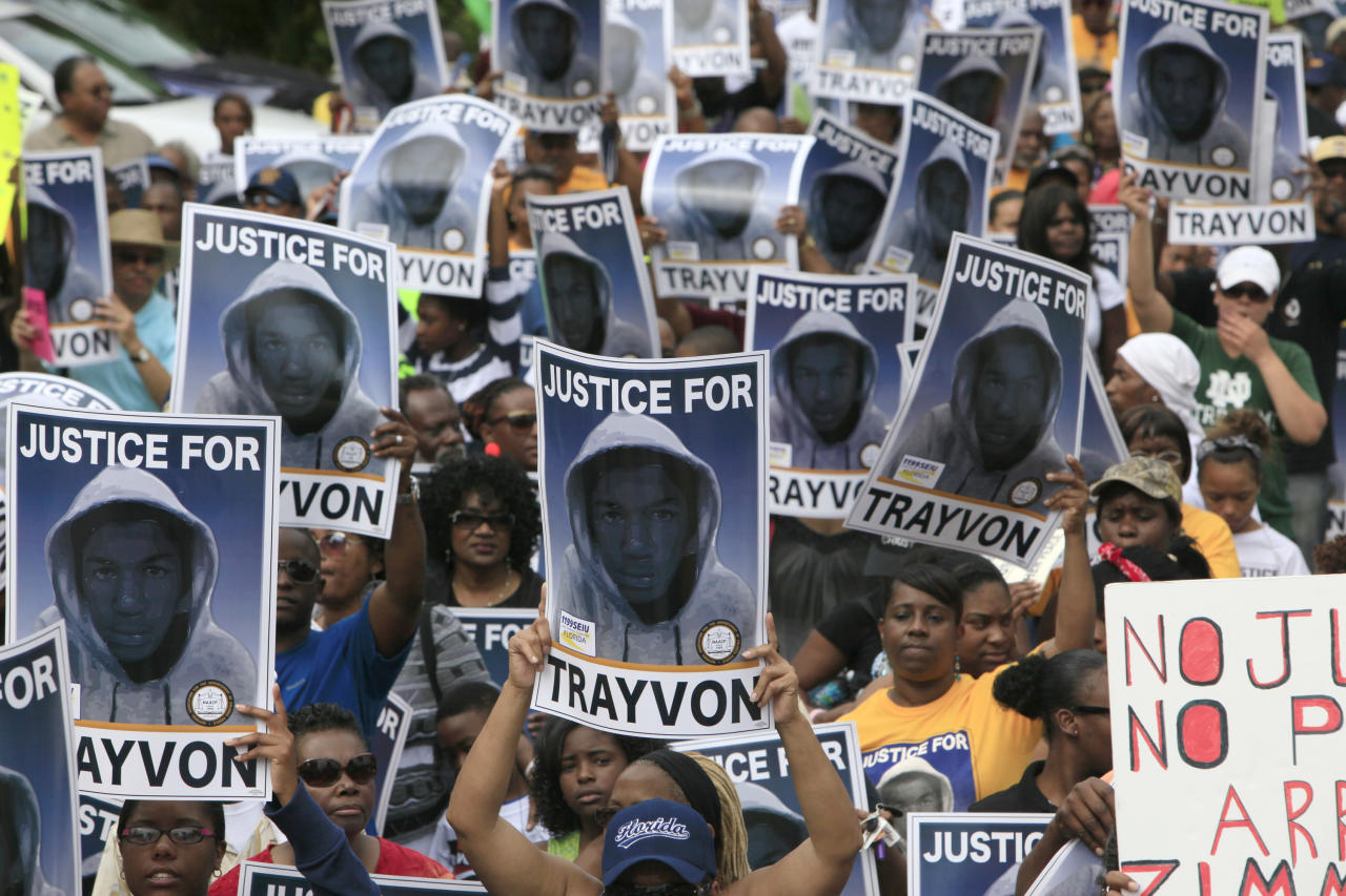 "Protesters hold signs during a march and rally for slain Florida teenager Trayvon Martin on Saturday, March 31, 2012 in Sanford, Fla. Protesters carried signs, chanted ""Justice for Trayvon,"" and clutched the hands of their children while they walked from Crooms Academy of Information Technology, the county's first high school for black students, to the Sanford Police Department. The march was organized by the NAACP and was one of several taking place over the weekend. Martin was shot to death by 28-year-old George Zimmerman on Feb. 26 as he walked from back from a convenience store to his father's fiancée's home in a gated community outside Orlando. (AP Photo/Julie Fletcher)"