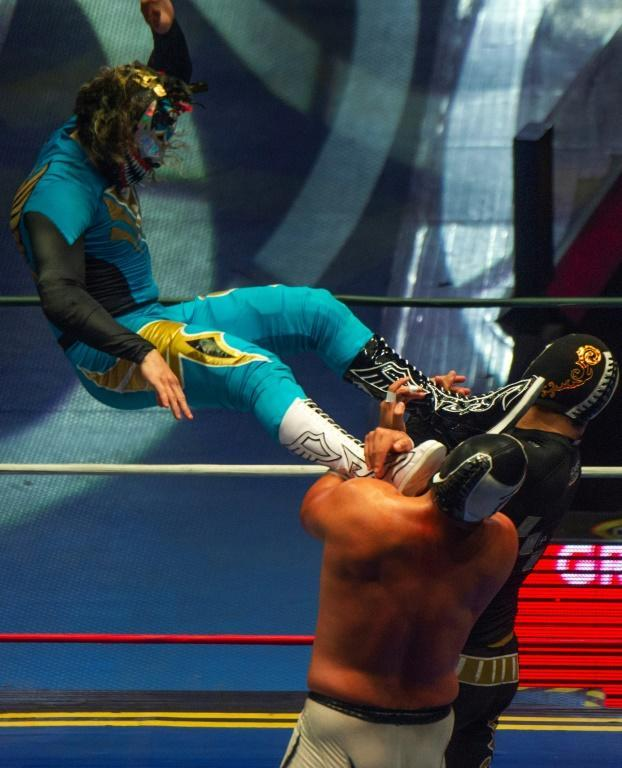 Wrestlers fight during an event in Mexico City's Arena Mexico on May 28, 2021 as an improved Covid situation has allowed the return of pro wrestling