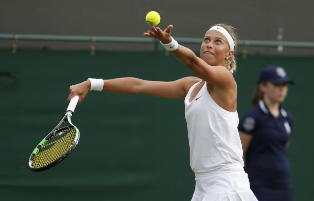 Andrea Hlavackova of the Czech Republic serves to Petra Kvitova of the Czech Republic during their first round match at the All England Lawn Tennis Championships in Wimbledon, London, Monday, June 23, 2014. (AP Photo/Alastair Grant)