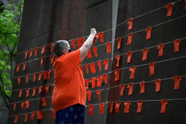 Orange fabric cut in the shape of shirts is pinned to string during a vigil in Ottawa June 5, 2021 to honour the 215 children whose remains were believed to found at the grounds of the former Kamloops Indian Residential School. A new federal holiday, the National Day of Truth and Reconciliation, will be marked on Sept. 30.  (Justin Tang/The Canadian Press - image credit)