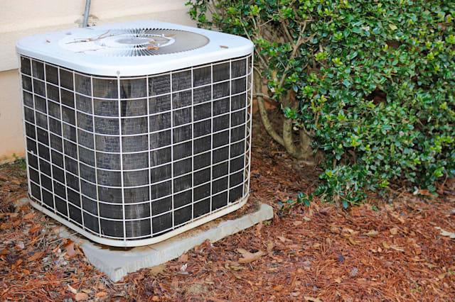 BYF01X Residential air condition unit in mulch near a home. Energy saving sustainable or eco-conscious products, exterior home e