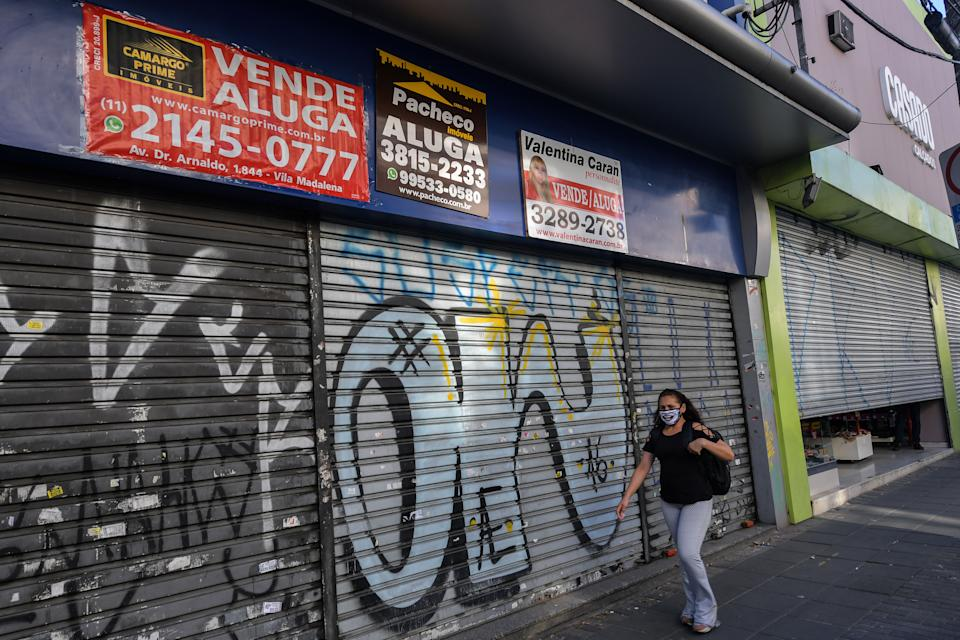 A woman walks past an empty store to rent or sell in a commercial area of Sao Paulo, Brazil, on June 17, 2020. - Sao Paulo is resuming its economic activity, but in some streets of Brazil's largest metropolis a succession of low iron curtains is evidence of the impact of the coronavirus: merchants have closed down. (Photo by NELSON ALMEIDA / AFP) (Photo by NELSON ALMEIDA/AFP via Getty Images)