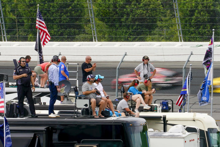 Fans watch from camper roofs as cars streak behind them during a NASCAR Cup Series auto race at Pocono Raceway, Saturday, June 26, 2021, in Long Pond, Pa. (AP Photo/Matt Slocum)