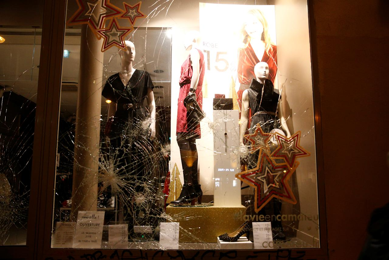"""A broken fashion store front window is seen at the end of a national day of protest by the """"yellow vests"""" movement in Paris, France, December 8, 2018. REUTERS/Stephane Mahe"""