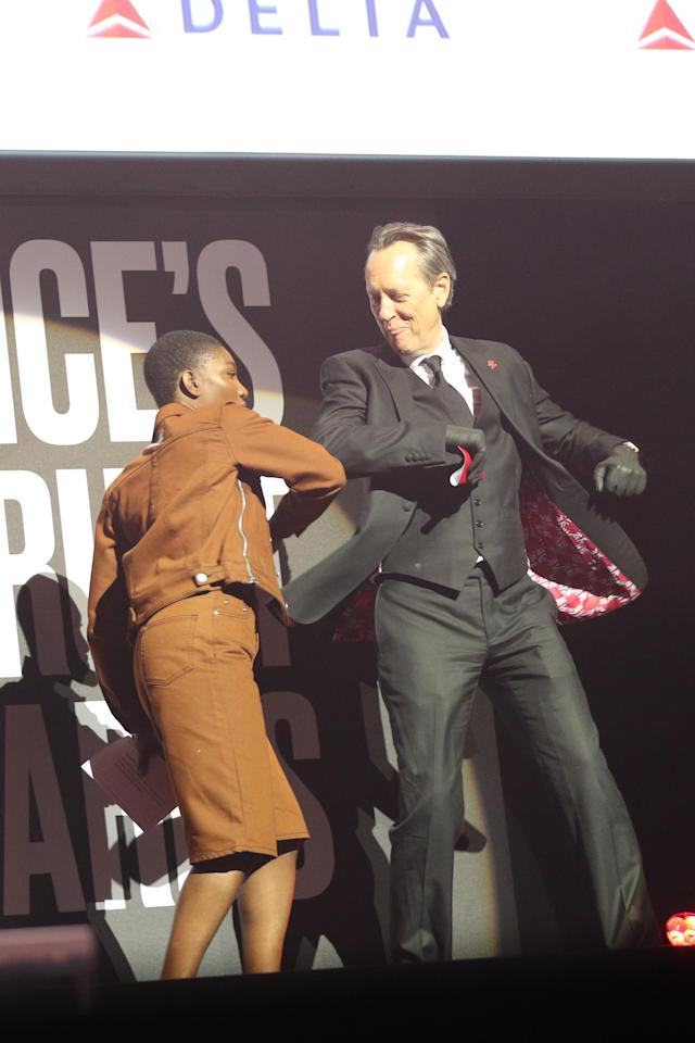 Michaela Coel and Richard E Grant elbow bump as they take to the stage to present an award. (Press Association)