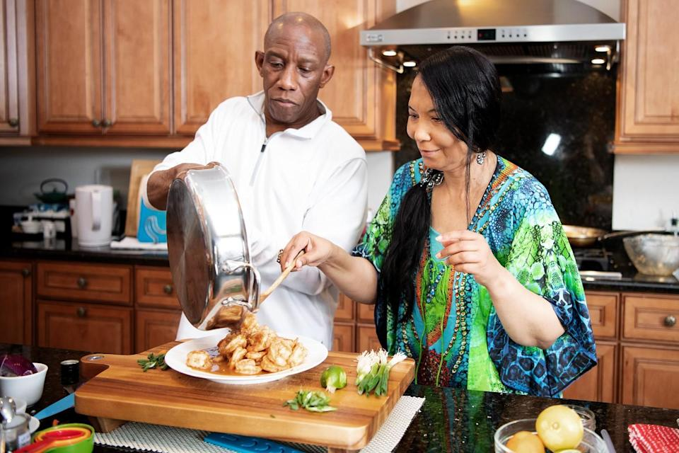Regina Mitchell's husband, Stan, tilts a pan while Mitchell uses a wooden spoon to put shrimp on a plate.