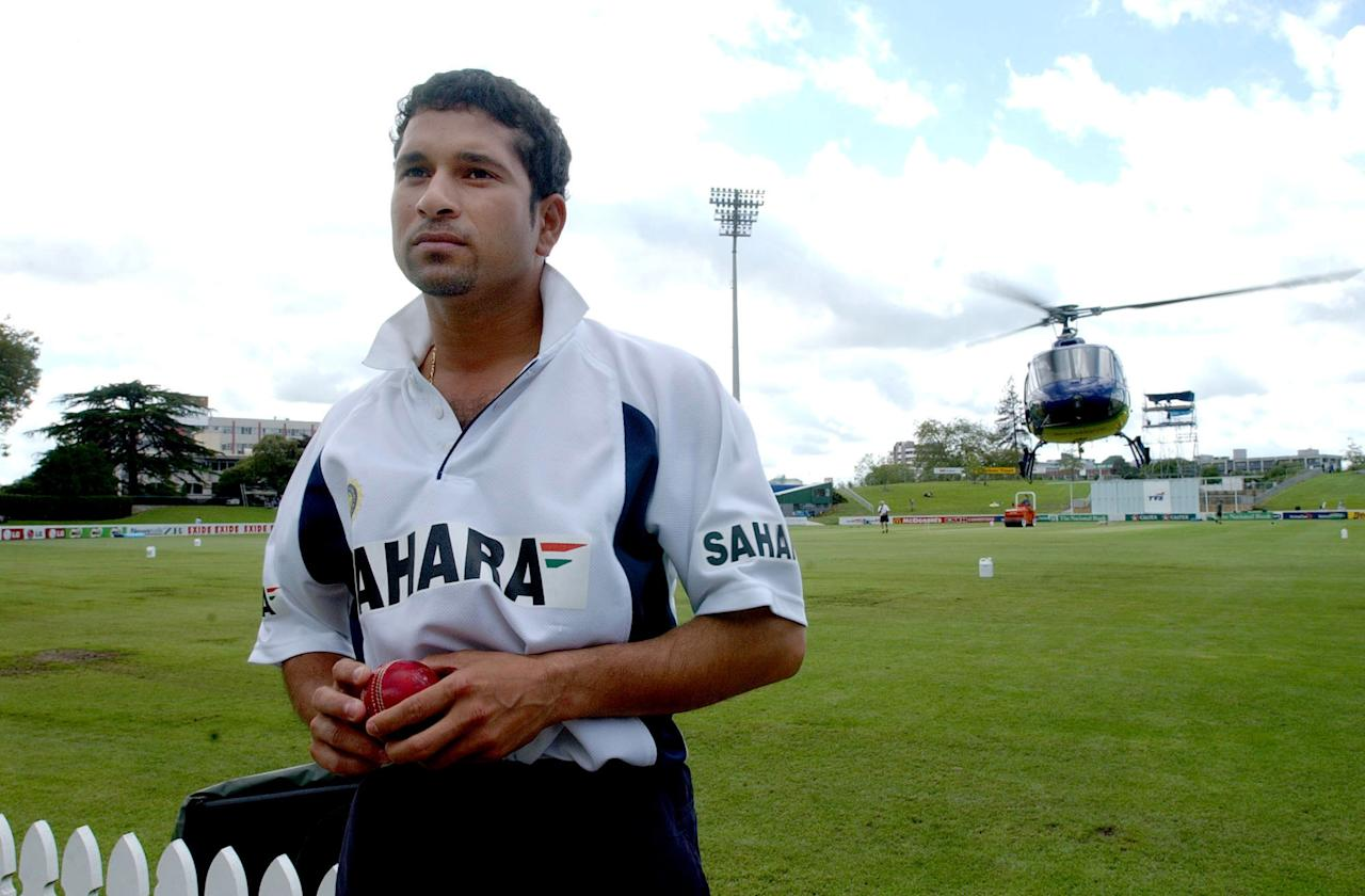 HAMILTON, NEW ZEALAND - DECEMBER 20:  India medium pace bowler Sachin Tendulkar looks on as a Helicopter does some low flying over Westpac Park to help dry out the field before day two of the second Cricket Test between the TelstraClear Black Caps and India played at Westpac Park, Friday. Day one of the 2nd Cricket Test match was called off yesterday because of bad weather.  (Photo by Dean Purcell/Getty Images)