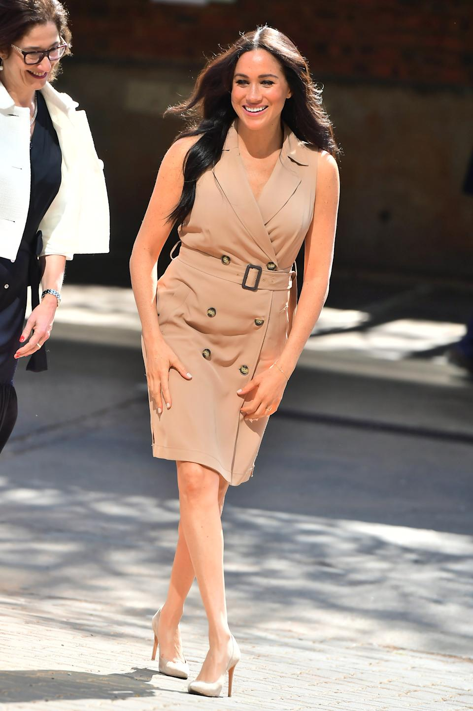 """During a morning in Johannesburg, Meghan wore a tonal tan took that featured a <a href=""""https://fave.co/2ndQaQZ"""" rel=""""nofollow noopener"""" target=""""_blank"""" data-ylk=""""slk:£95 trench dress by Banana Republic"""" class=""""link rapid-noclick-resp"""">£95 trench dress by Banana Republic</a>. She paired it with Stuart Weitzman shoes and dainty gold jewellery. <em>[Photo: Getty]</em>"""