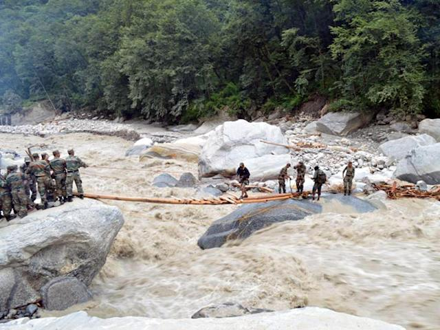 In this handout photograph received from the Ministry of Defence (MOD) on June 27, 2013, Indian defence personnel assist stranded civilians in crossing a raging river near the Pindari Glacier area of northern Uttarakhand state. Rescue workers stepped up the search for bodies June 27 in India's flood ravaged north, as mass cremations of victims already discovered got underway amid fears of outbreaks of disease , officials and reports said. AFP PHOTO / MOD