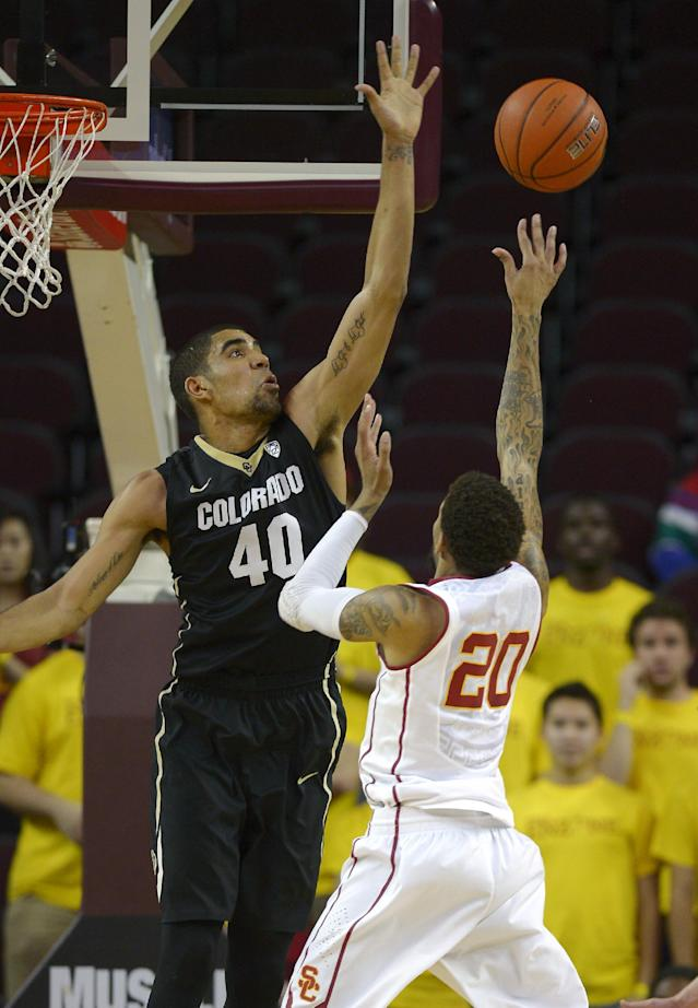 Colorado forward Josh Scott, left, rejects the shot of Southern California guard J.T. Terrell during the first half of an NCAA college basketball game, Sunday, Feb. 16, 2014, Los Angeles. (AP Photo/Mark J. Terrill)