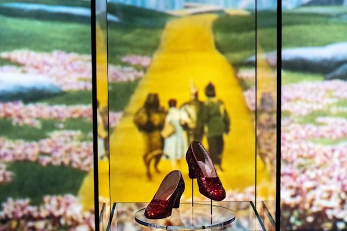 Ruby shoes in a glass case, with a photo of the Yellow Brick Road in the background